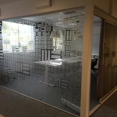 Glasparti på konferensrum hos Modern Ekonomi. Mönster inspirerat av deras logo.
